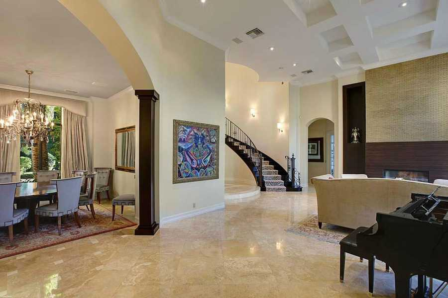 Breathtaking open layout is graced with neutral marble floors that flow from the formal living and dining areas to the wide open casual side.