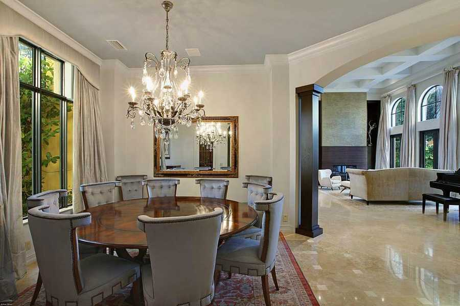 Formal dining room features molded ceilings and sits eight around this beautiful wooden table.