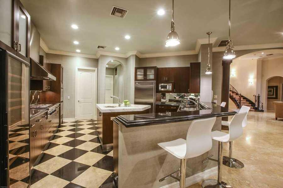 Custom kitchen features very modern appliances.