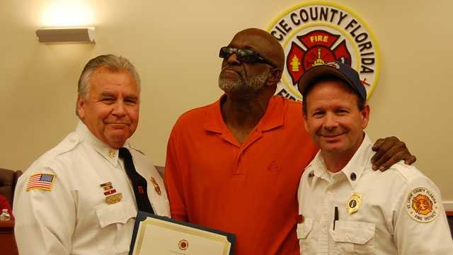 St. Lucie County Fire District Chief Ron Parrish and Lt. Tommy Neiman present Tommy Barber (center) with the Citizen Hero Award.