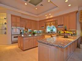 A customized kitchen features expansive cabinetry, the best appliances, and granite-topped cooking island.