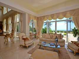 Formal living room features floor-ceiling windows and a priceless ocean view.