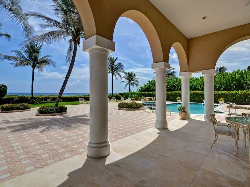 An expansive cabana resides next to the home's grand pool and jacuzzi .