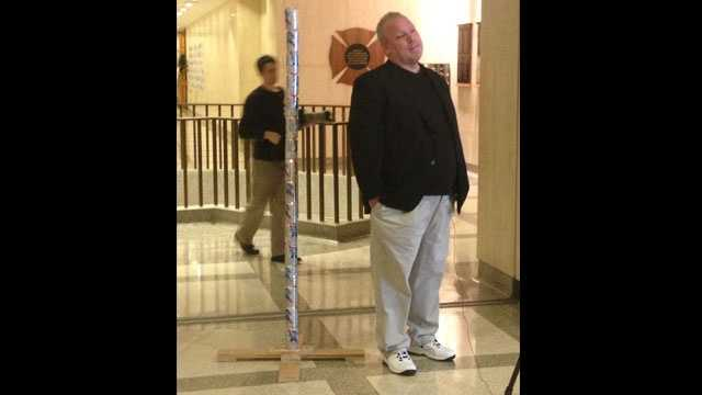 Chaz Stevens proudly stands next to his 6-foot-tall Festivus pole made of empty Pabst Blue Ribbon cans.