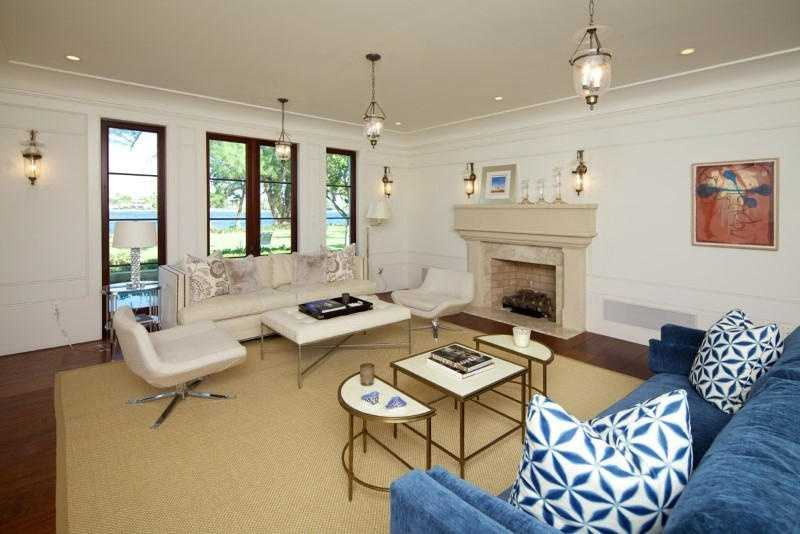 Living room features a minimal, sophisticated style, fireplace and multiple windows.