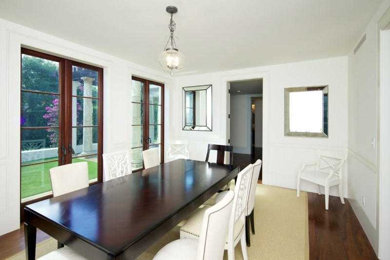 Formal dining room features a beautiful dark wood table.