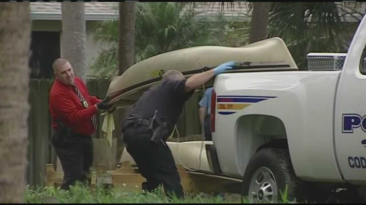 Detectives take a canoe from the Patricia Danna-Harrison's home into evidence.