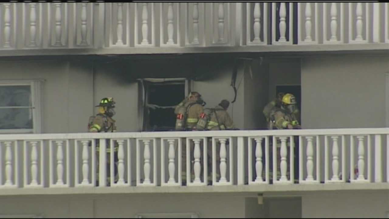 Firefighters work to clean up after flames damaged a vacant unit at this Lake Park high-rise condo.