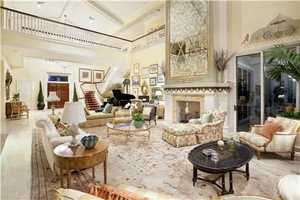 Directly ahead, the dramatic two-story living room highlights a fireplace with massive antique mirrored over-mantel and a soaring window wall capturing sweeping water vistas
