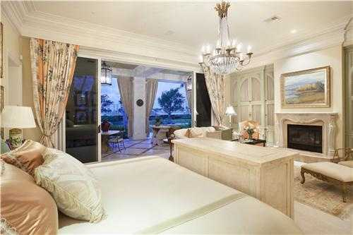 Lavish master bedroom features a fireplace and private patio entrance.