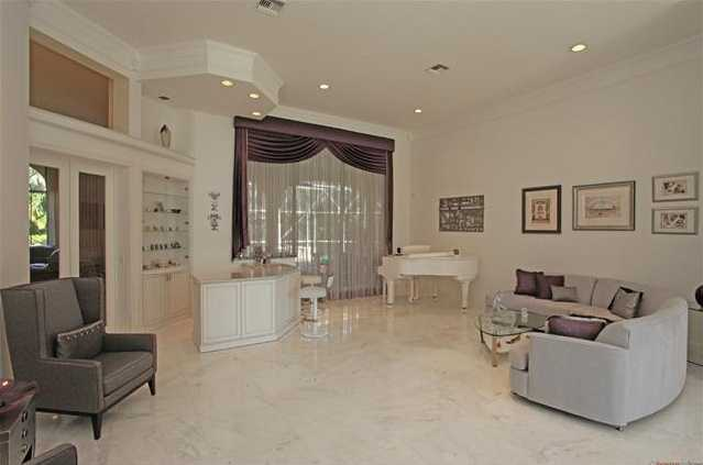 Marble foyer leads into an elegant, white living room featuring a bar for classy soirees.