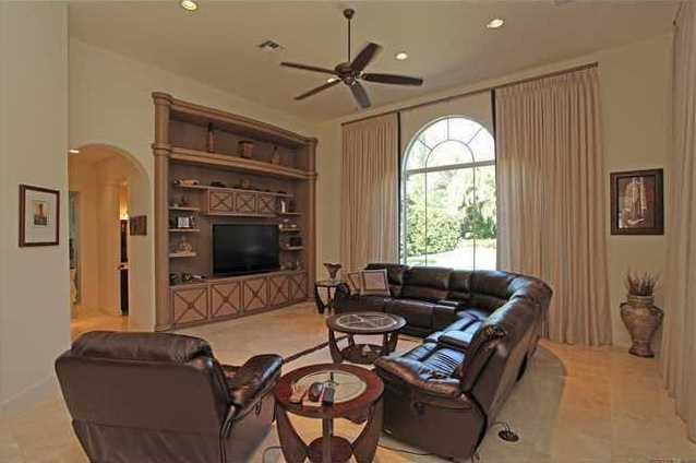 Family room features a custom entertainment unit and floor-to-ceiling window.