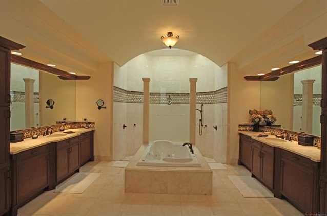 The master bathroom is suitable for a king and queen. It includes separate vanities, a large spa tub, and an even larger shower.