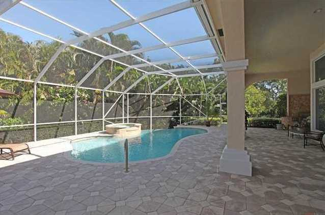 This pool area is screened in to provide some shade and includes a summer kitchen.