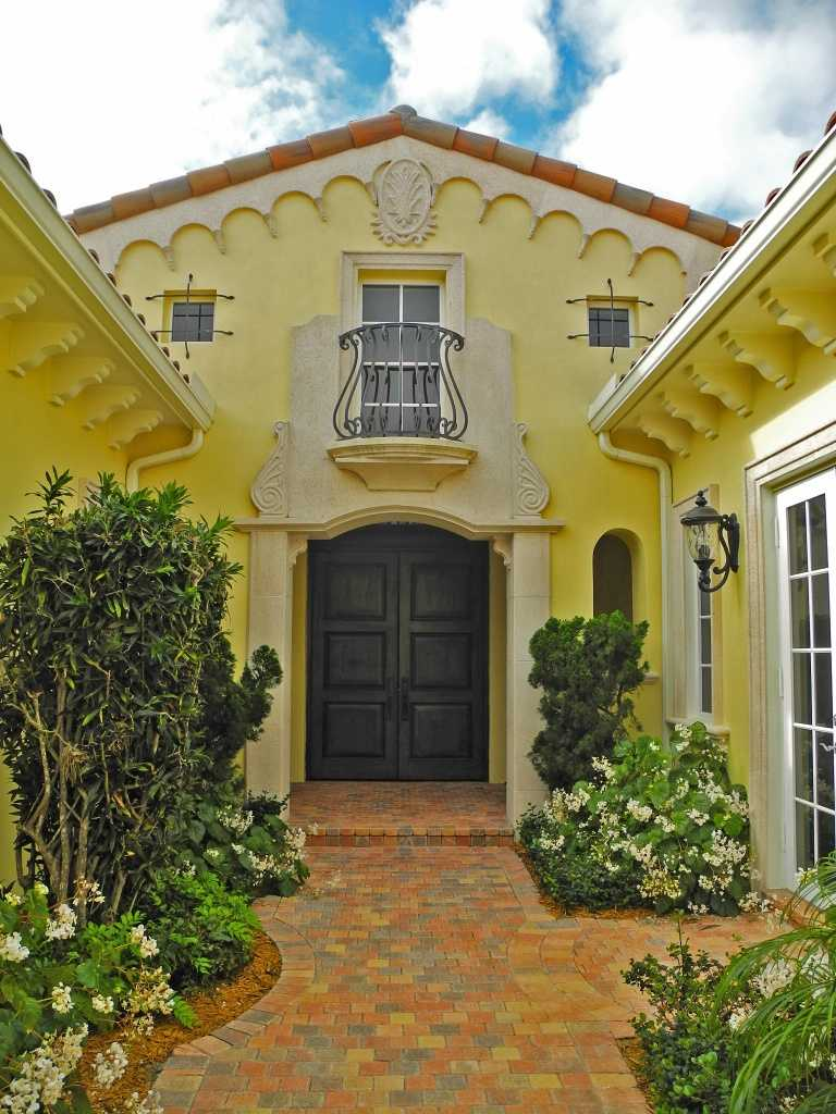 """The chic yellow paint adds an """"Old Florida"""" charm to this exclusive property."""
