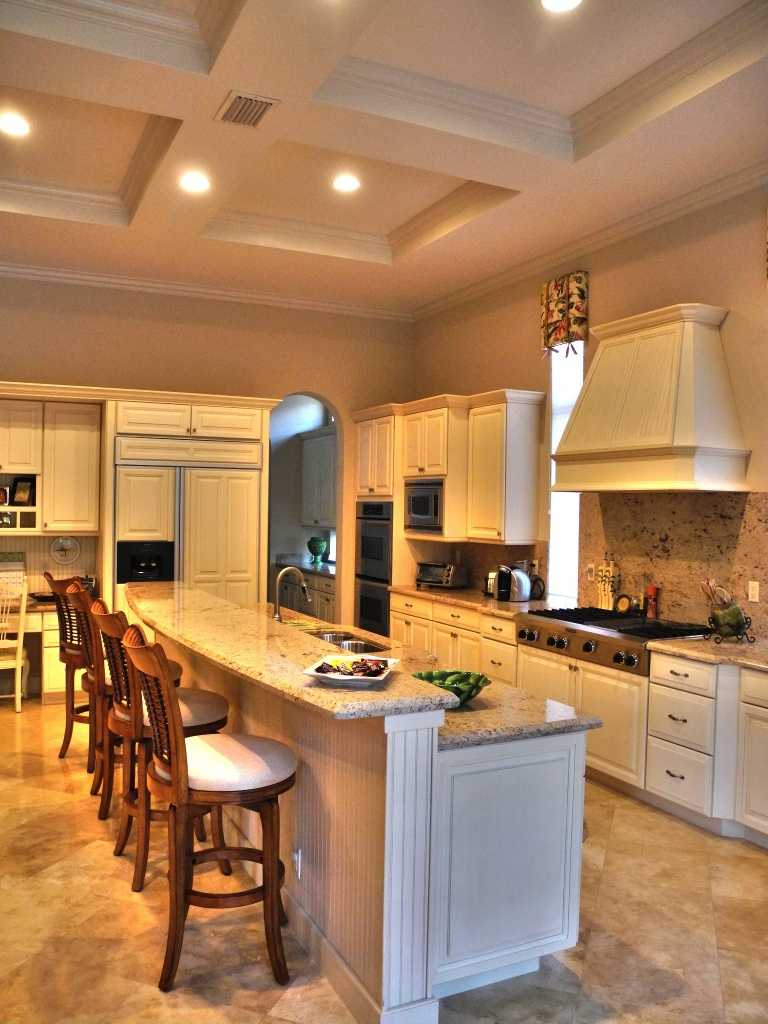 A remodeled kitchen features an elongated, granite-topped dining bar and top-off-the-line appliances.