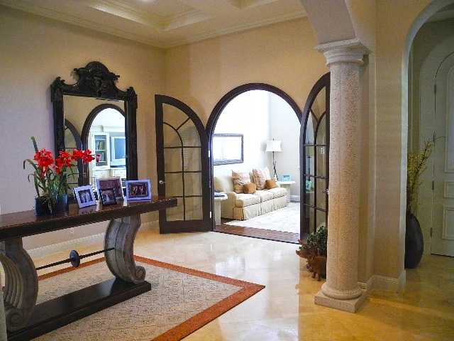Arched, French doors lead you to a comfortable family room.