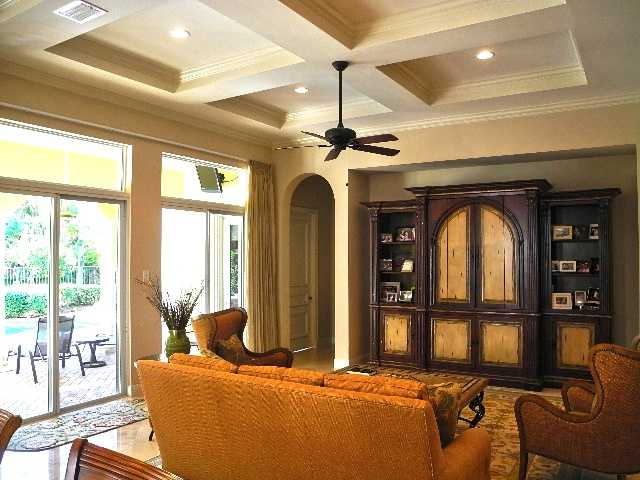 This living space features a beautiful ceiling, access to the patio, and rich, vintage inspired decor.