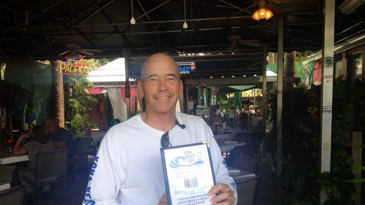 Frank Wacha displays his menu for this weekend's event in which he'll be serving shark to commemorate the two-year anniversary of his brush with a shark.