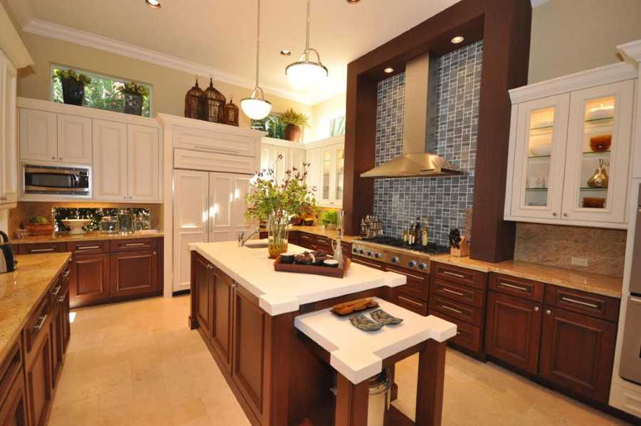 A commercial grade kitchen with limestone center work island, granite counter-tops, stainless appliances including stainless hood/fan.