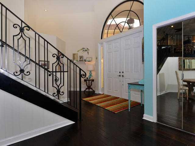 In foyer showcases beautiful walnut floors and a custom-railed staircase.