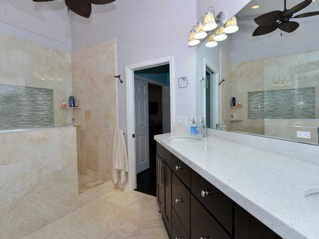 The walk-in shower is non-traditional and tiled perfectly. While the vanity sinks offer immense counter space.