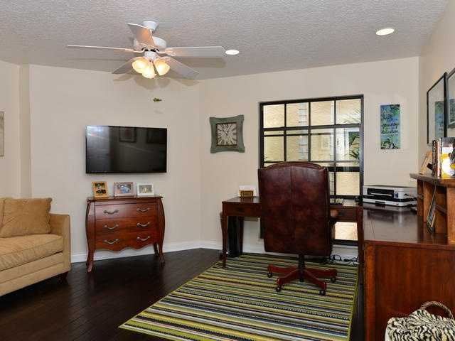Home office features an L-shaped desk along the window and traditional decor.