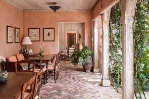 Rustic-themed lanai boasts hanging vines and brick flooring.