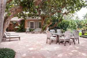 Family dinners can be spent under the branches of lush trees by the pool.
