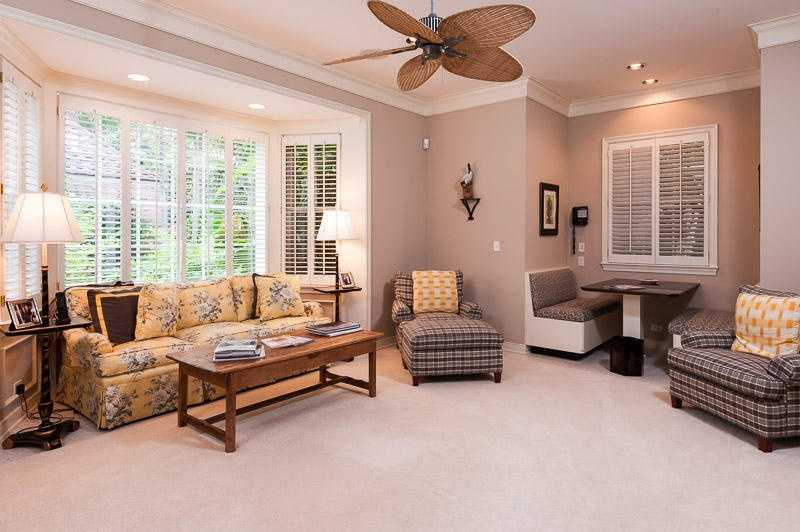 Couch in this space is nestled along a bay window.