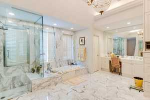 Wow! Wall to floor marble is featured in this deluxe space.