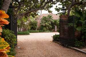 Lush, tropical plants surround the gateway and driveway.