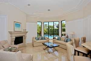 When you enter the home, the first thing you see are the polished marble floors leading into the living room, which features vaulted ceilings, beautiful fireplace/mantle, and sparkling pool views.