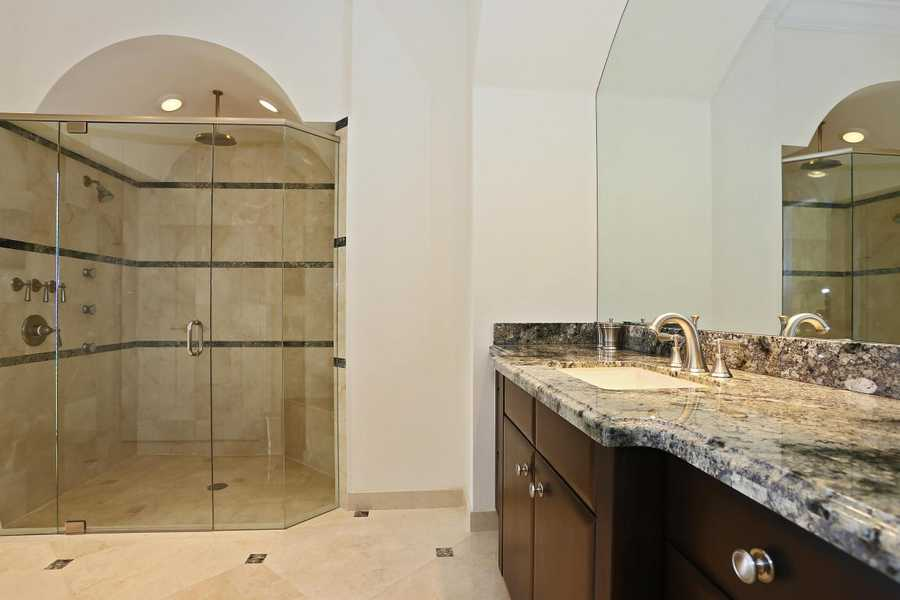 A darker marble top contrasts with the lighter tile in the generous shower.