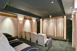 Home theater is complete with comfy reclining seats for eight and a large scale projector screen.