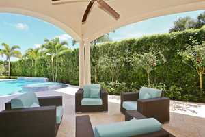 Tranquil patio/pool is surrounded by lush greenery for privacy.