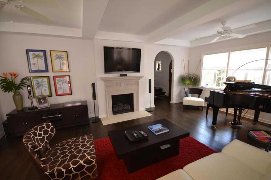 Living room has gas fireplace with original carved mantel. Hardwood floors and custom ceilings throughout.
