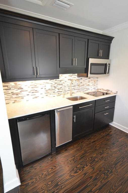 The kitchenette features hardwood floors, dark cabinets, and tile backsplash.