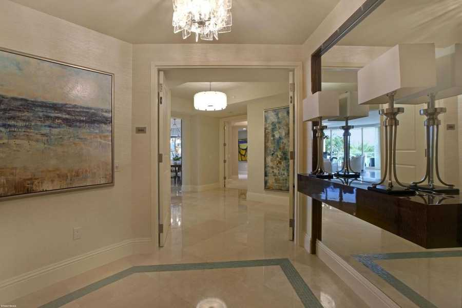 The beautiful foyer features a mirrored wall and pricey accents without coming off as gaudy.