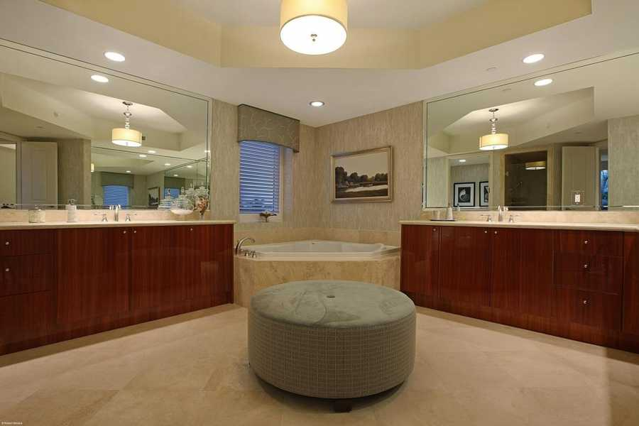 Master suite boasts a massive spa tub placed between gorgeous dual vanity areas.