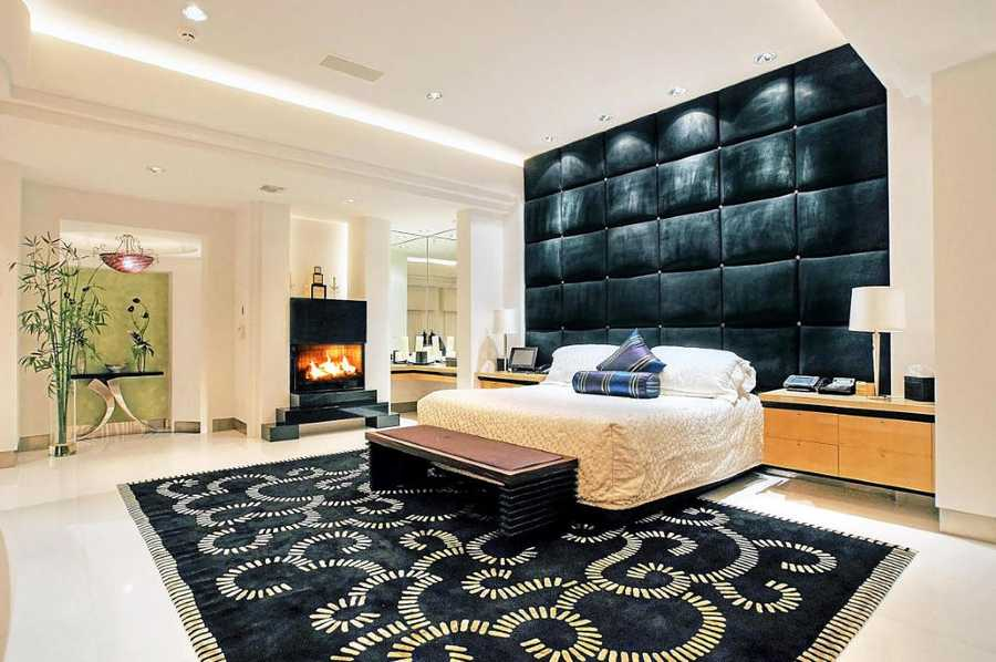 Master suite boasts a fireplace and ceiling-high, tufted headboard.