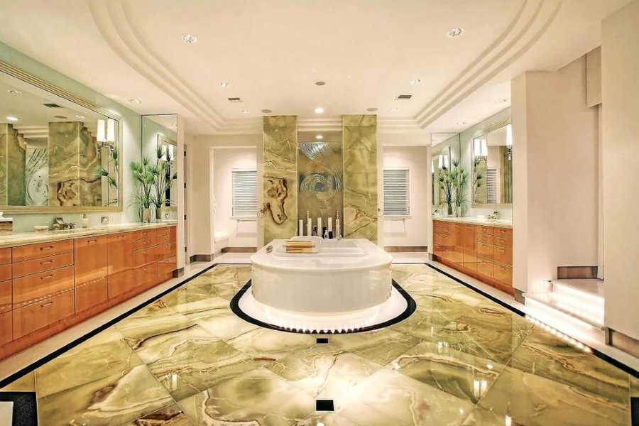 Marble floors and wall piece add a soothing elegance to the master bathroom.