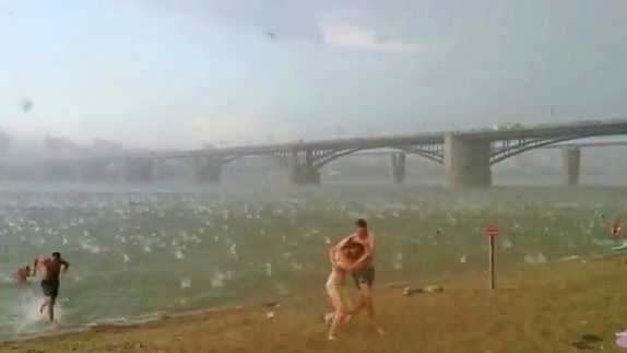 Sudden freak hail storm in Siberia causes beach goers to run for safety.