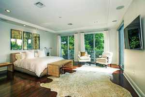 The generous master bedroom features a balcony overlooking the pool.
