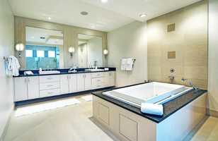 The sunlit master bathroom also features lovely dual vanities.