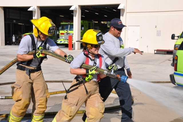 Reporter Stephanie Berzinski takes on the power of the water hose during training exercises with Palm Beach Gardens Fire Rescue.