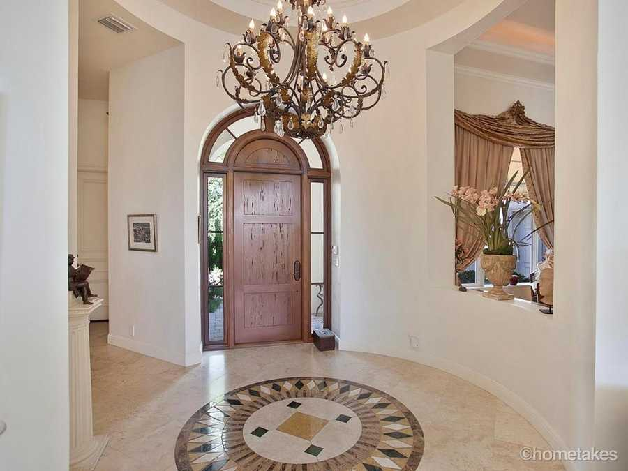 Beautiful foyer boasts a bold chandelier above a complimentary tile pattern.