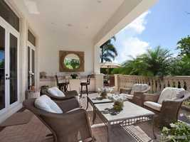 The living room opens out to the a gorgeous classic lanai with summer kitchen.