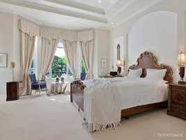 Master suite features an elegant vaulted ceiling and seating area.
