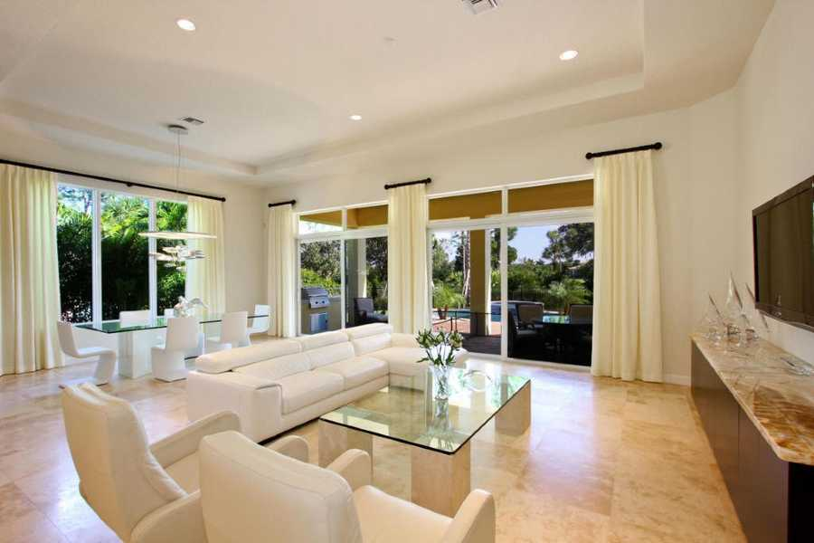 The living room boasts beautiful floors, recessed lighting, and floor-to-ceiling windows overlooking the pool.